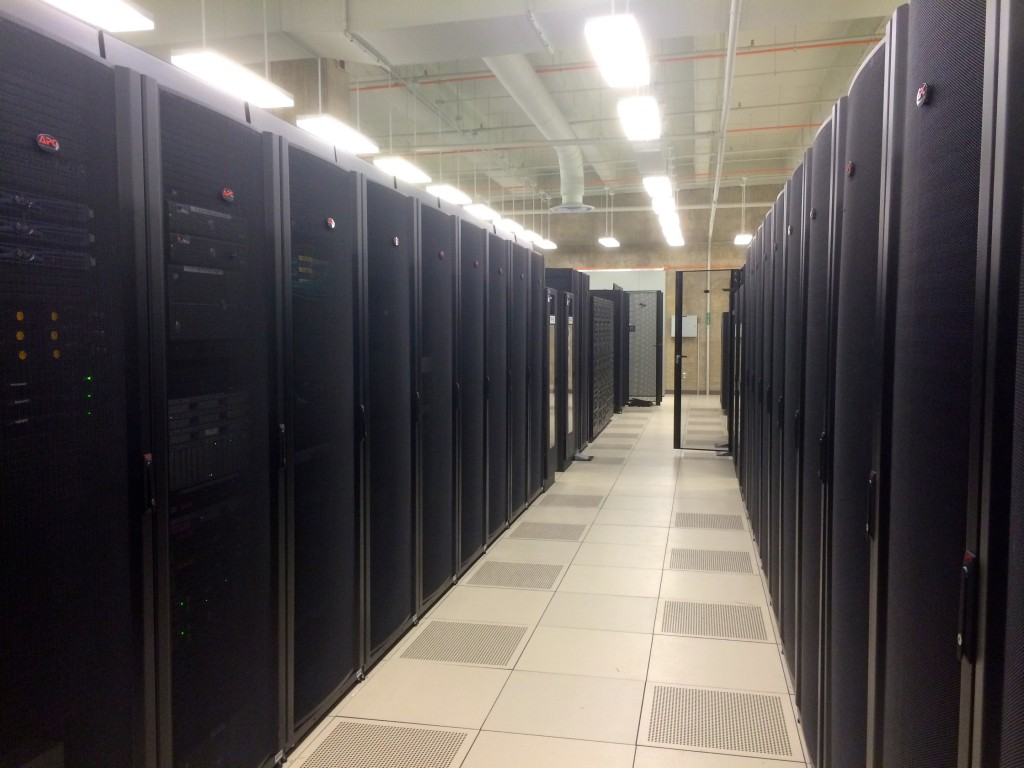 Here are two long rows of server racks in one of the main server pods. Each rack holds multiple computers, as well as sometimes running thousands of virtualized instances of servers.